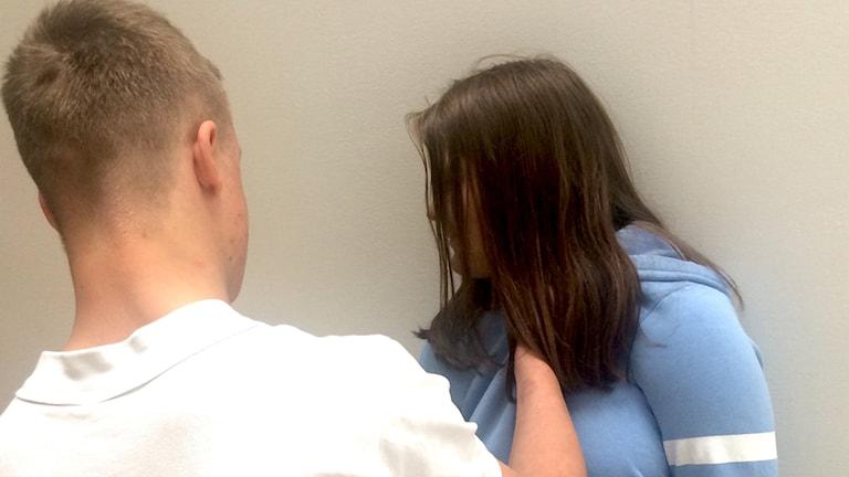 En anonym man tar på en anonym tjej som vänder sig bort.