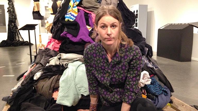 Anna-Lisa Persson framför hög av kläder