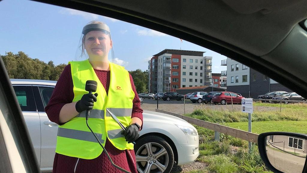 Kvinna med mikrofon och reflexväst