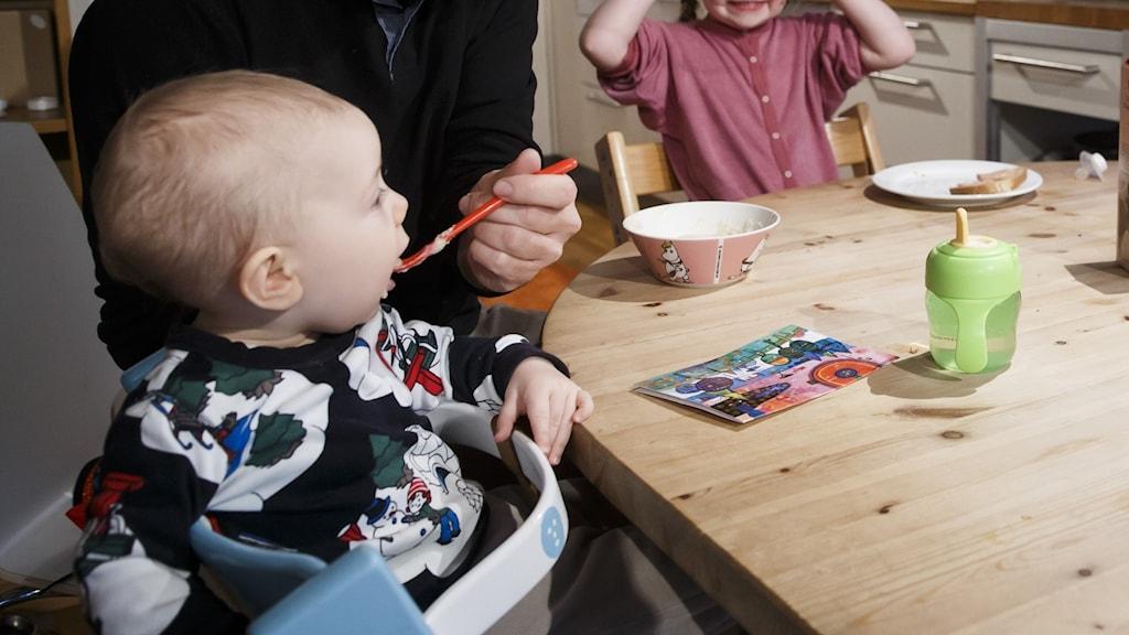 Barn som får mat vid ett köksbord