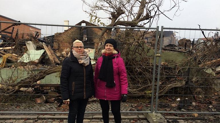 Margareta Widerberg och Birgitta Rosander, framför brandresterna och det gamla blåregnet.