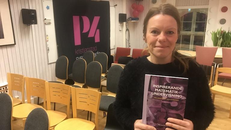 Kvinna håller i bok.