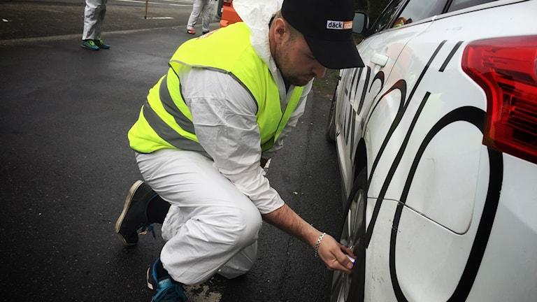 Man i reflexväst står på knä vid en bil och kontrollerar bakdäcket.