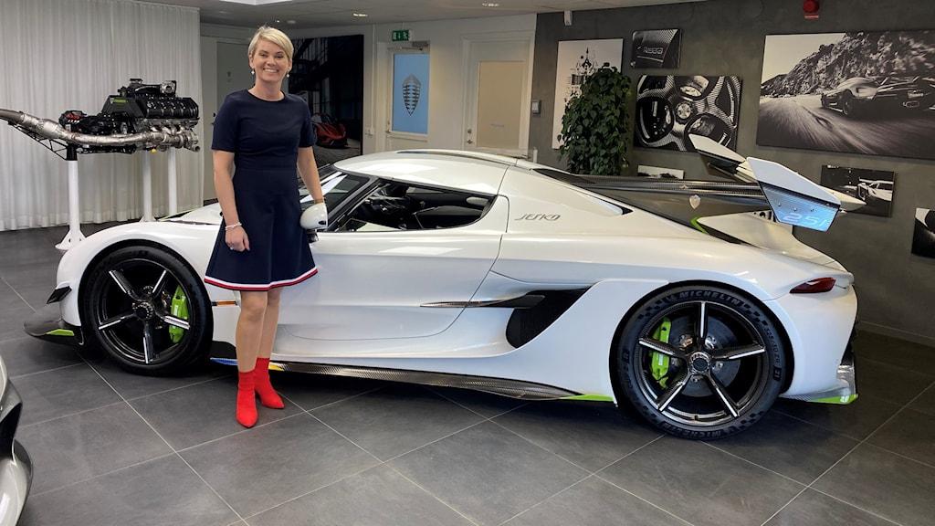 Kvinna som står inomhus vid en sportbil.
