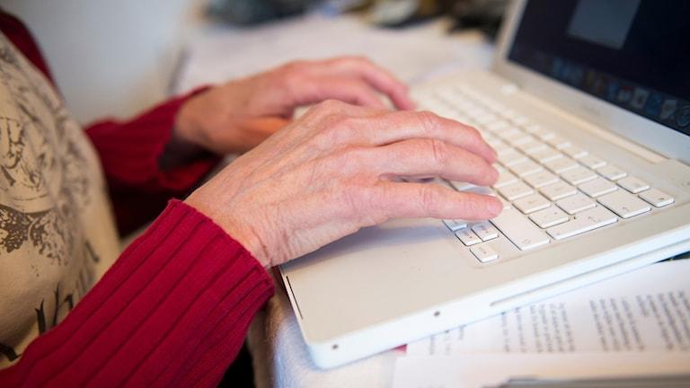 Äldre kvinnas händer på tangentbord