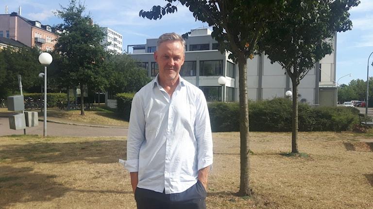 Per Dahlberg står framför hus och träd