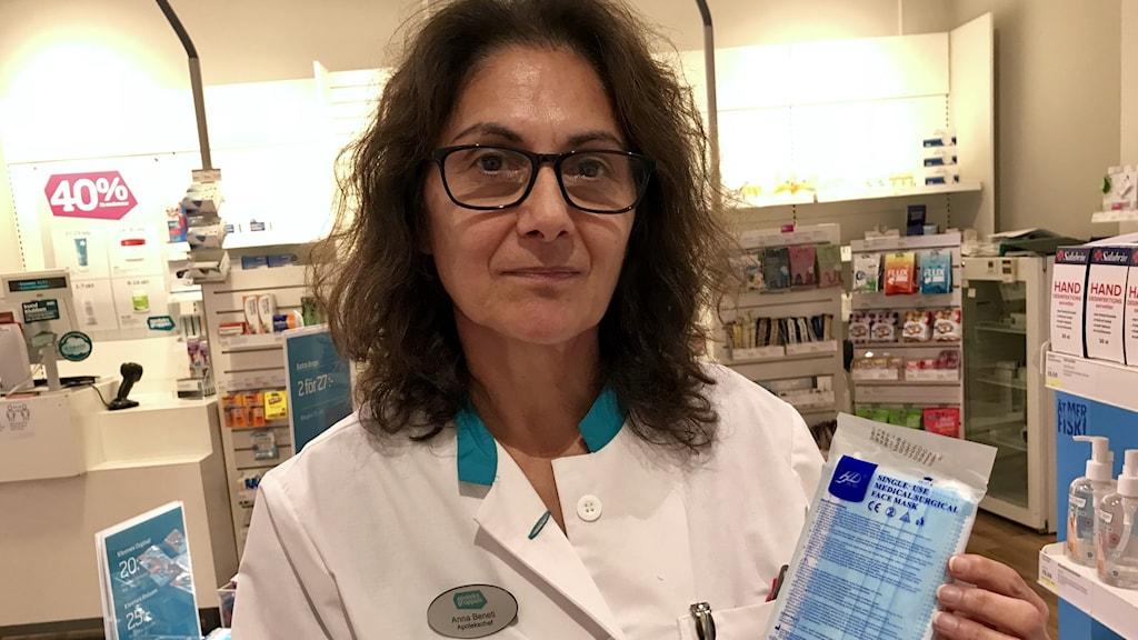 Kvinna i apoteksrock på ett apotek med munskyddsförpackning i handen