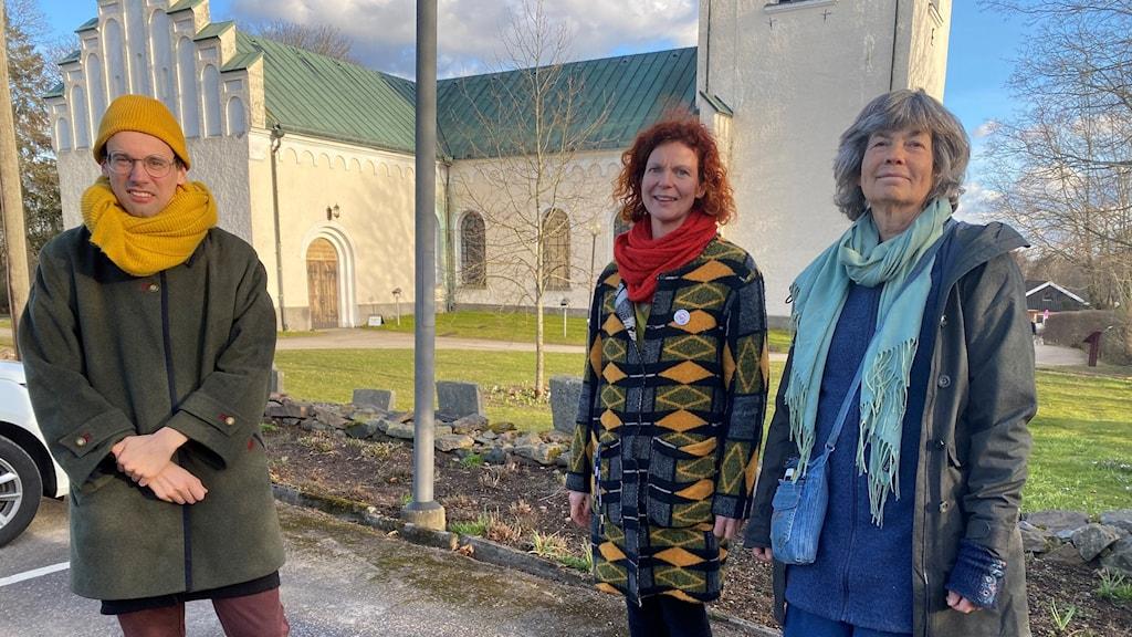 Tre personer framför en kyrka.