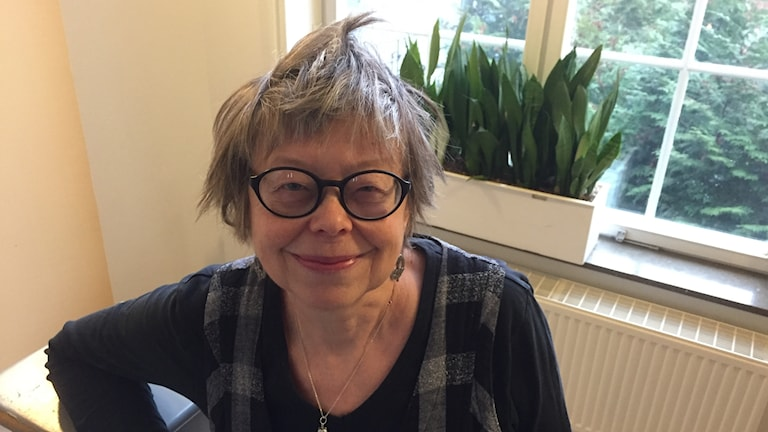 Kvinna med kort grått hår och glasögon