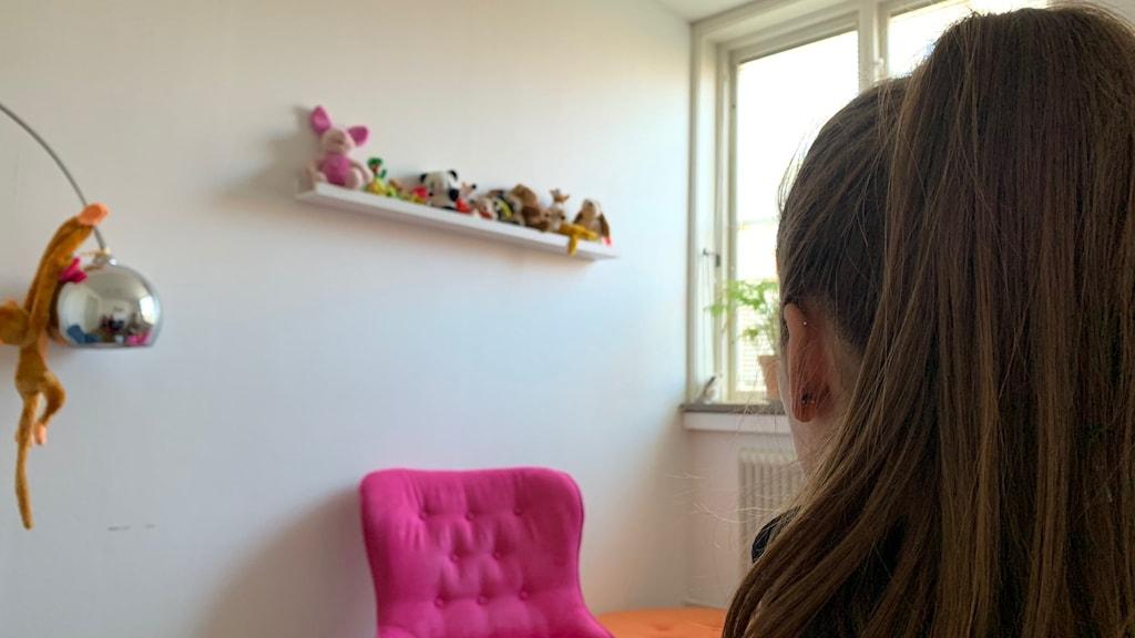 Kvinna bakifrån i rum på kvinnojour med gosedjur.
