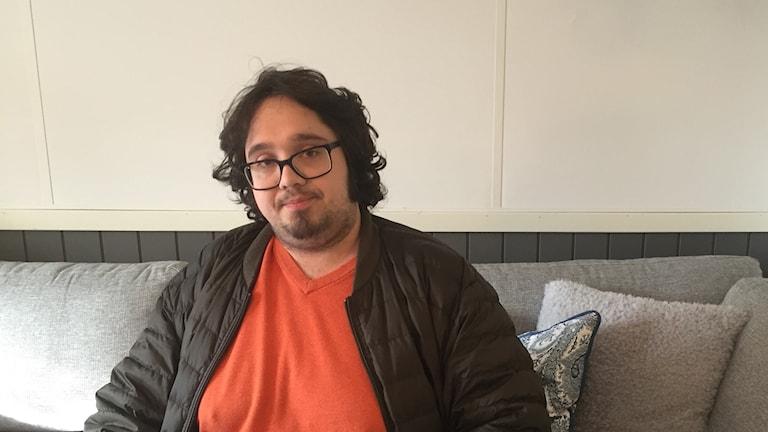 Man med lockigt mörkt hår och orange tröja sitter i soffa.