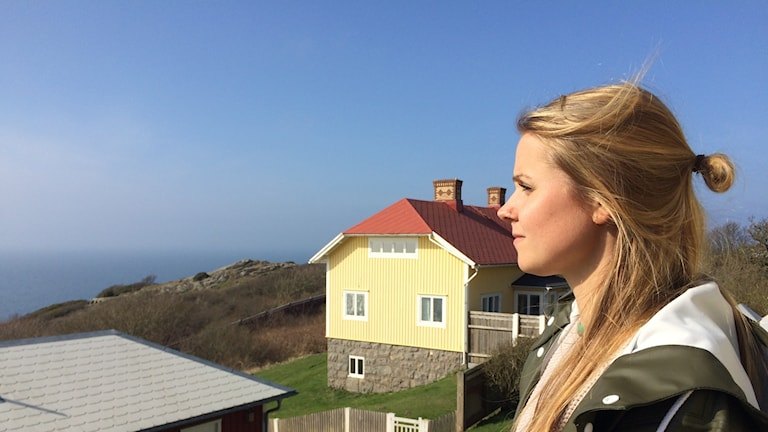 Kvinna med långt hår tittar ut över ett hav.