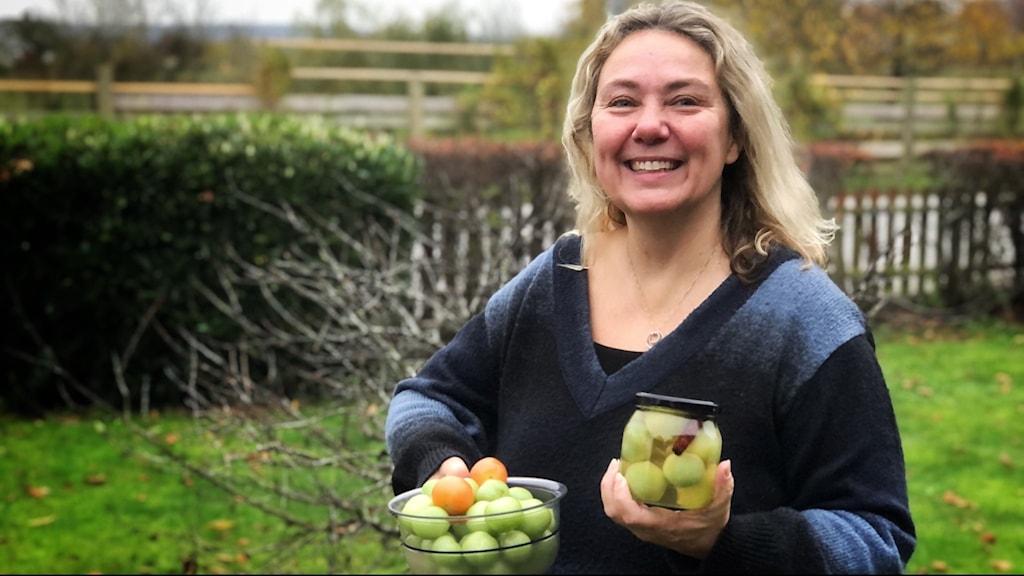 Kvinna håller i skålar med tomater.
