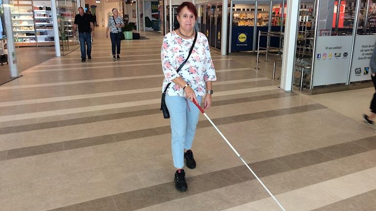 Kvinna med vit käpp i shoppingcenter