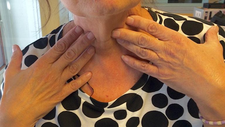 En kvinna pekar på sin sköldkörtel med båda händerna.