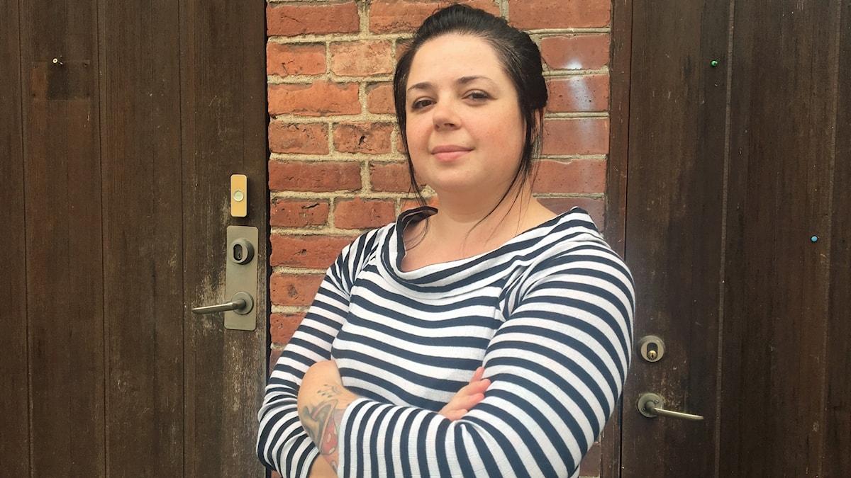 Kvinna står med armar i kors vid en lägenhetsingång