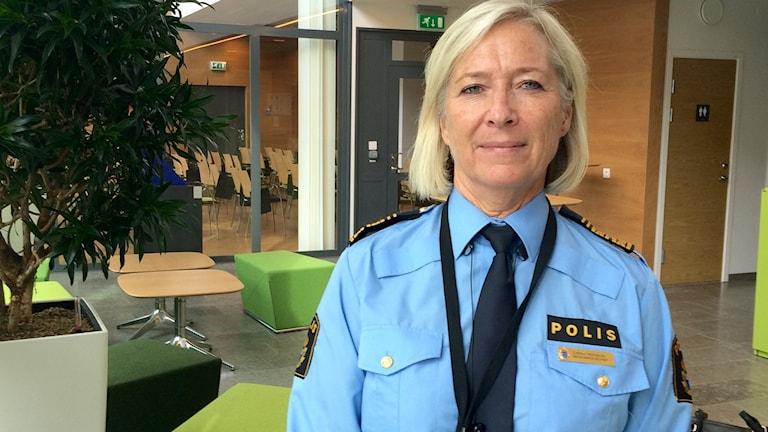 En kvinna i ljust hår fotas framifrån i poliskläder.