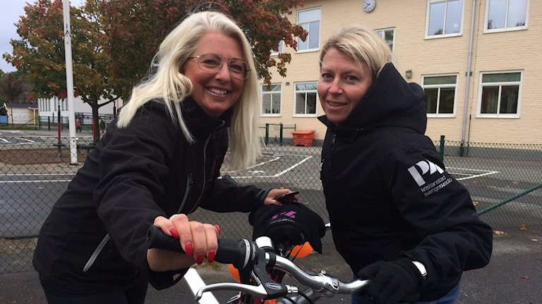 Två blonda kvinnor vid en cykel