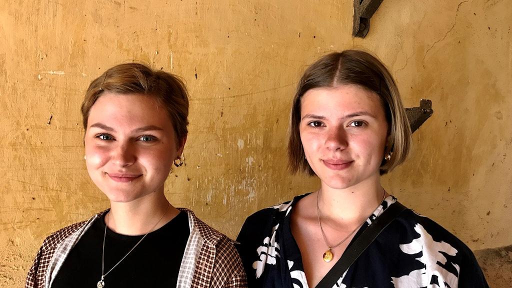Två unga kvinnor mot en gul vägg