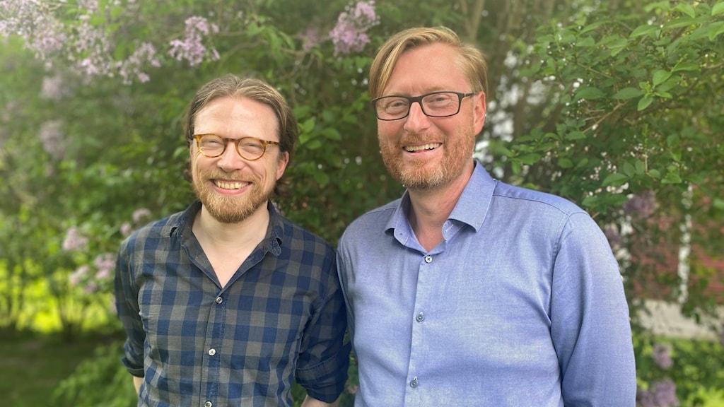 Två män med glasögon framför syrénbuskar.