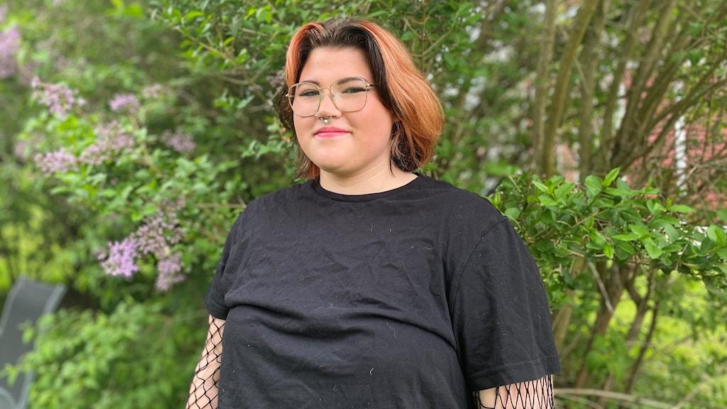 Ung kvinna med glasögon som står utomhus, med buskar i bakgrunden.