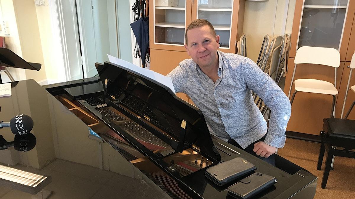 Man som sitter vid piano.