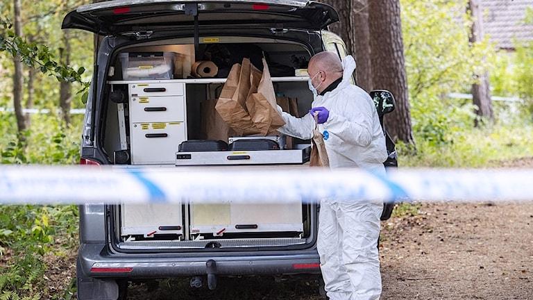 Polisens tekniker lastar in bevis i sin bil.
