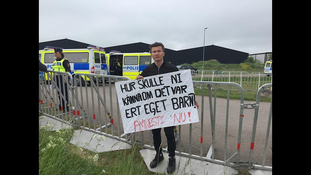 Arif Moradi med sin protestskylt utanför Migrationsverkets förvar i Åstorp.