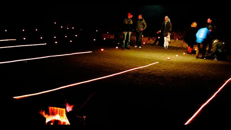 Människor spelar boule i mörkret.