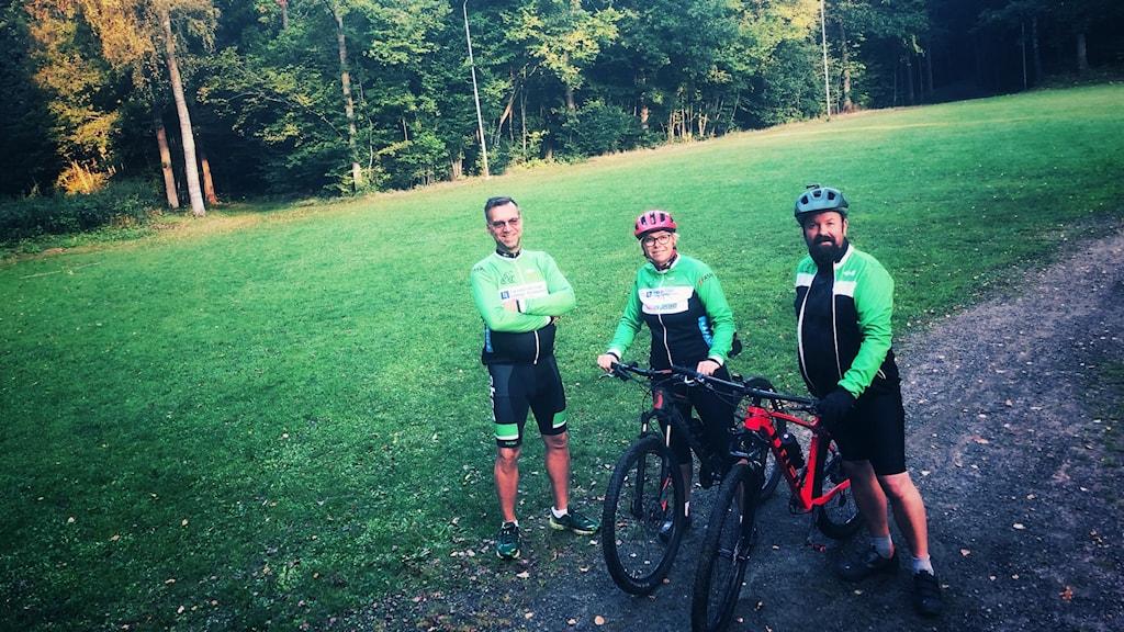 Tre människor med cyklar på en gräsmatta