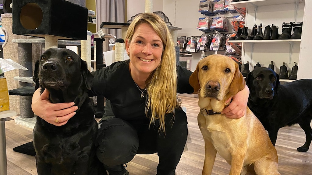 Kvinna står knäböjd och håller om två hundar.