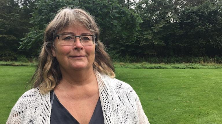 Kvinna med långt hår och glasögon i en trädgård.