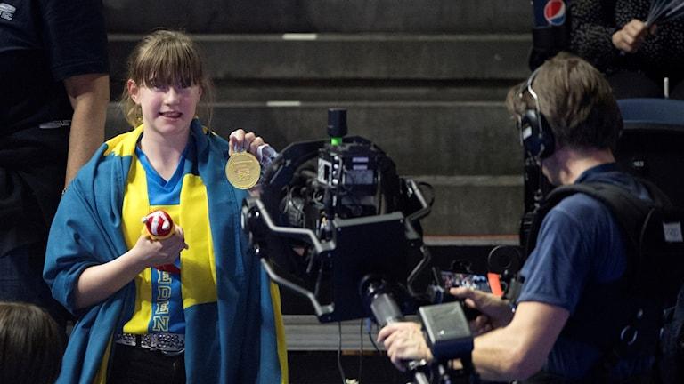 Flicka sträcker fram en guldmedalj.