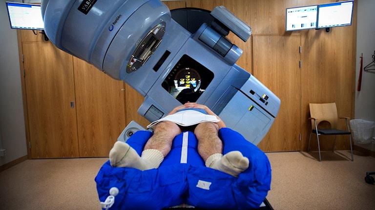 Man ligger på en brits och ovanför en strålbehandlingsmaskin.