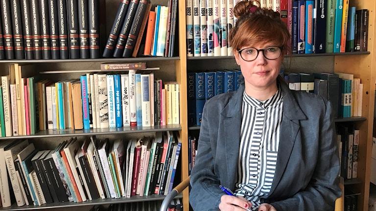 Kvinna framför bokhylla