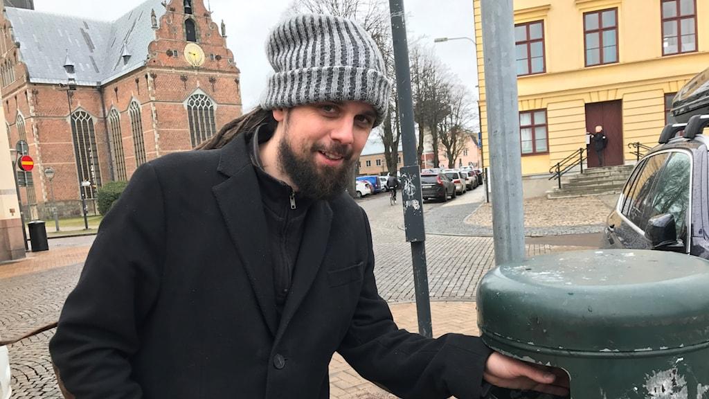 Andreas Jakobsson, man med mössa stoppar handen i en papperskorg för att leta sopor.