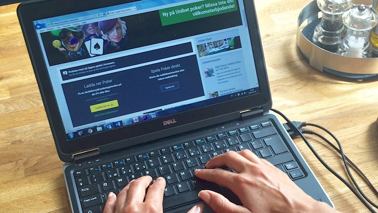 En peson sitter framför en dator och är inne på en spelsajt.