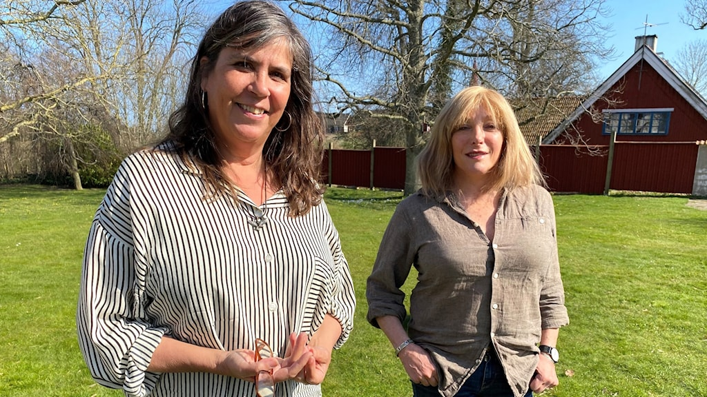 Två kvinnor i trädgård.