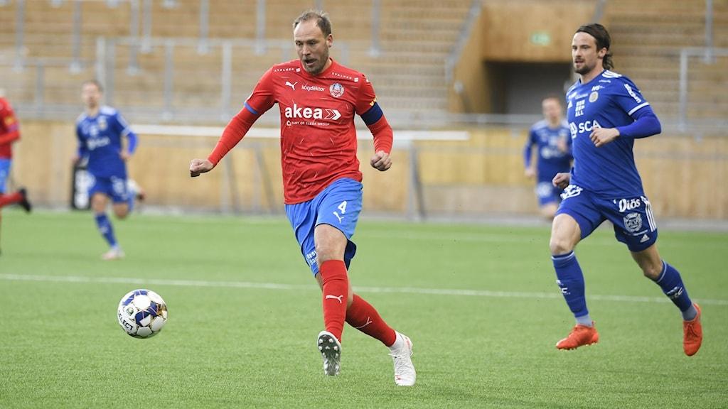 Rödtröjad fotbollsspelare med boll före spelare i blå kläder.