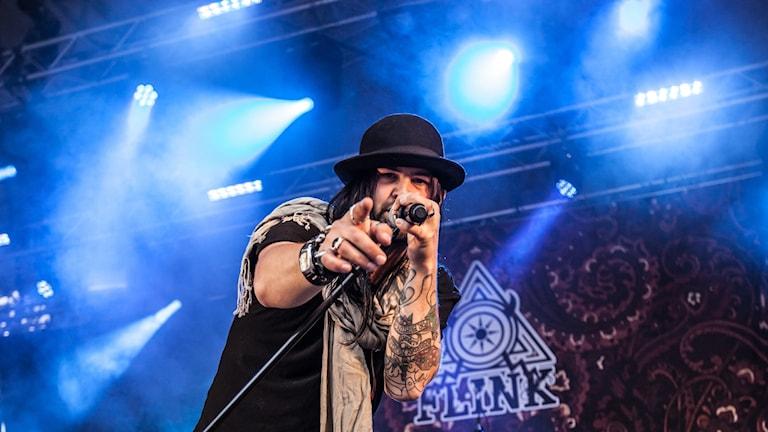 Man med tatueringar och hatt pekar in i kameran och sjunger i en mikrofon.