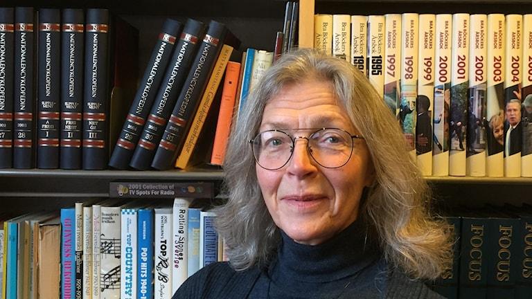 Kvinna med glasögon framför en bokhylla