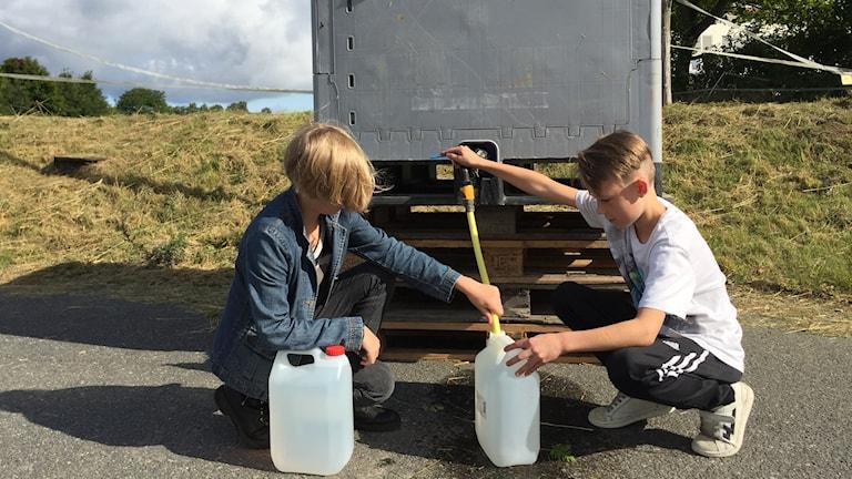 Skolbarn hämtar vatten i tank
