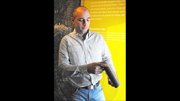 Hallandsås innehåller inte alltid gnejs av den kompakta sort som finns i den här borrkärnan som Skanska Vincis geolog Oskar Aurell tittar på.Foto: Gunilla Nordström/SR Kristianstad