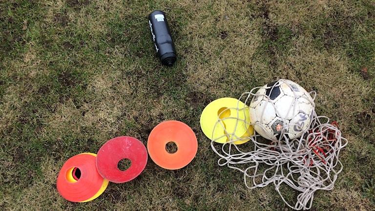 Fotboll, vattenfalska, nät och röda och orange brinkor på gräsmatta.