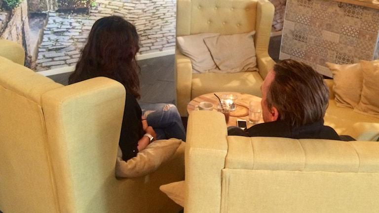 En kvinna och en man sitter vid ett runt bord, med ryggen mot kameran.