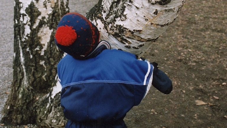 Ett barnmed ryggen mot kameran med overall håller om en björk.