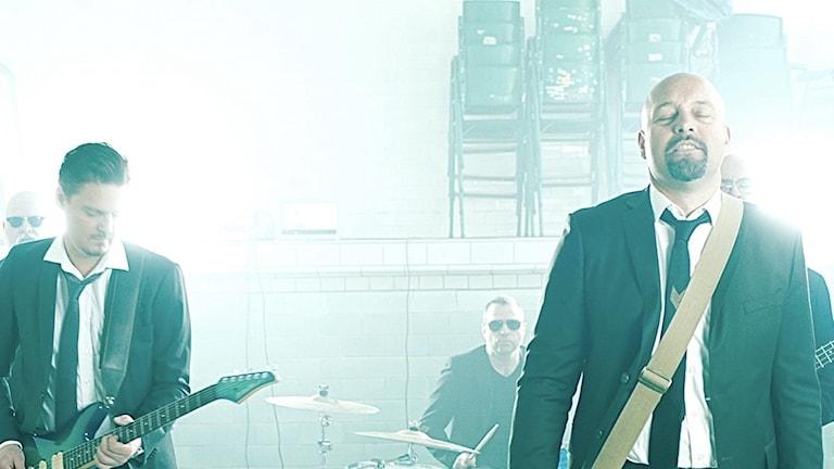 Fem män i mörka kläder som är riktade framåt och har instrument i sina händer.
