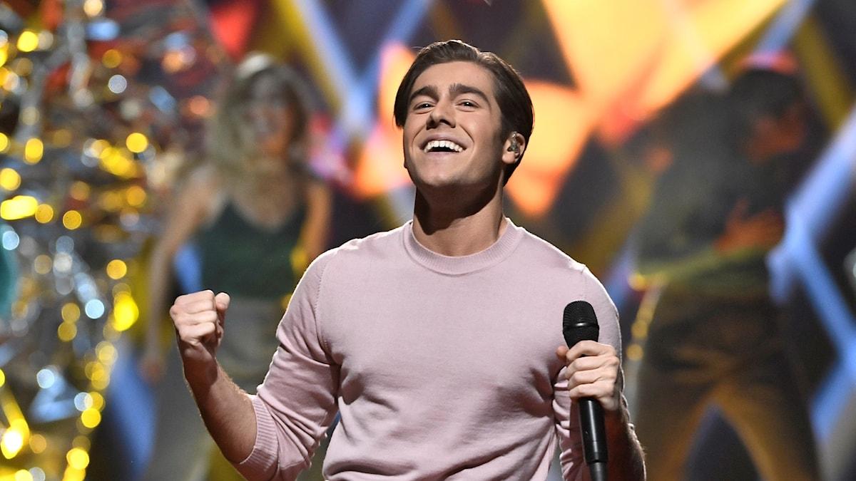 Ung man som ser glad ut med en mikrofon i ena handen.