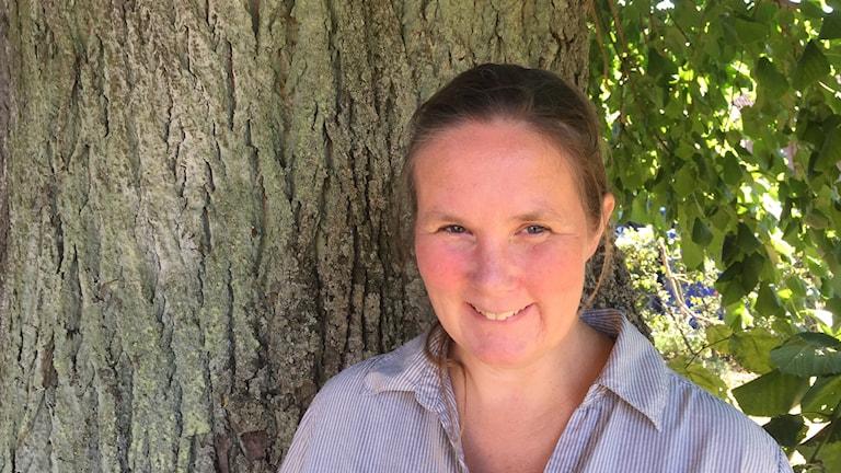 Kvinna med uppsatt hår som står framför en trädstam.