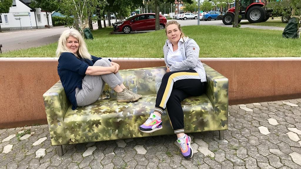 Två kvinnor sitter i en Klippansoffa av betong målad i gul-gröna nyanser